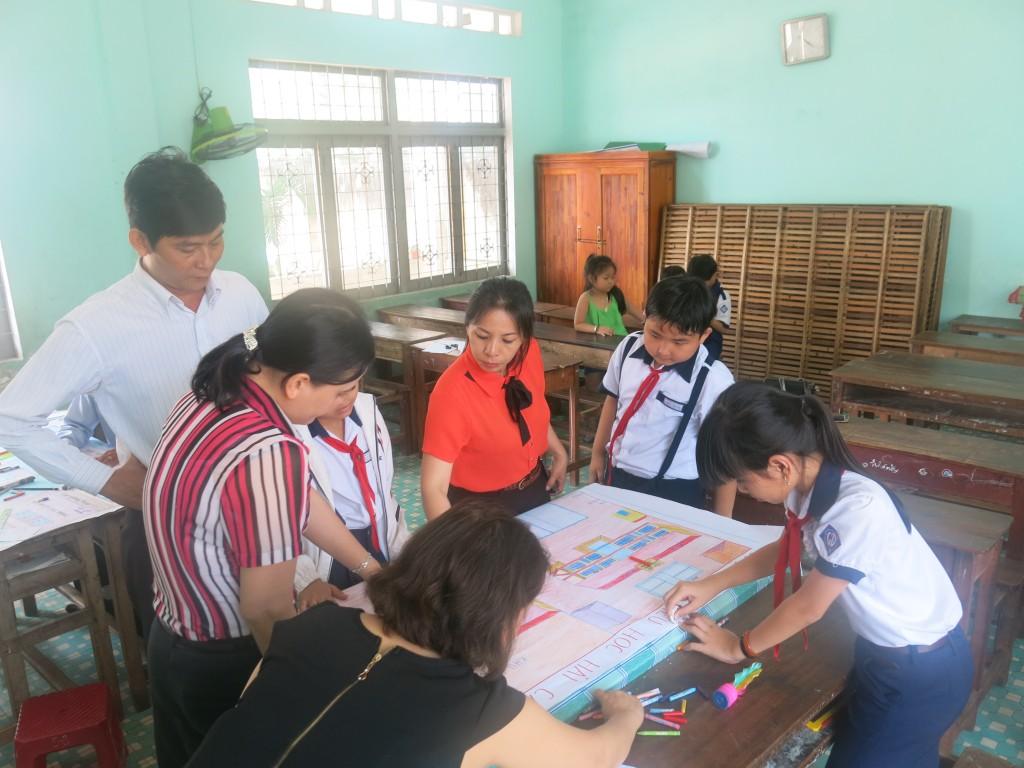Cô Hà (áo màu cam) đang cùng các em học sinh và phụ huynh vẽ sơ đồ trường tiểu học Hải Cảng và khu vực dân cư xung quanh trường